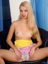Blonde girl undressing on the chair and showing her tits